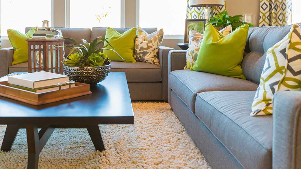 Furnished living room with grey couches, a coffee table, and green accent pillows