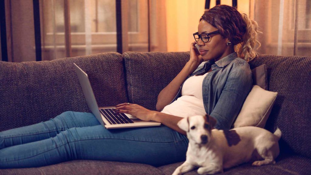 A woman sitting on the couch talking on the phone with a laptop and her dog next to her